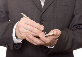 Close-up picture of businessman's hand writing in the business card